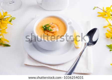 Creamy tomato soup with seafood and lemon on a white background.