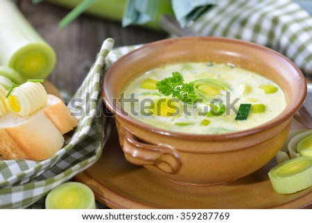 Creamy vegetarian cheese and leek soup with buttered baguette, served on a wooden table - stock photo