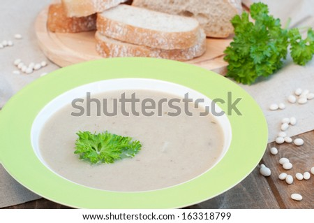 Creamy white bean soup with parsley and fresh bread, rustic style, horizontal - stock photo