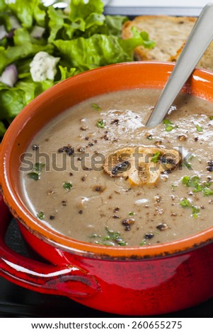 Creamy wild mushroom soup diner with garlic toast, lettuce salad, and a beer. - stock photo