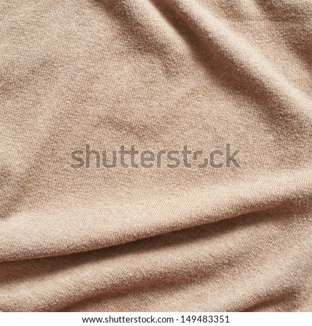 Creased beige cloth material fragment as a background texture - stock photo
