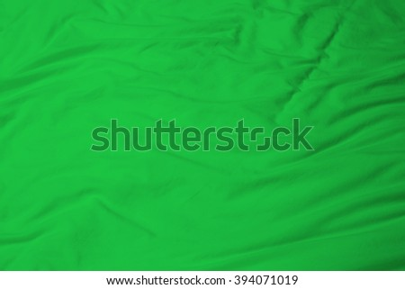 creased green cloth material fragment as a background. - stock photo