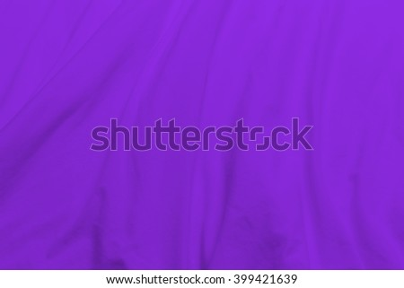 creased purple cloth material fragment as a background. - stock photo
