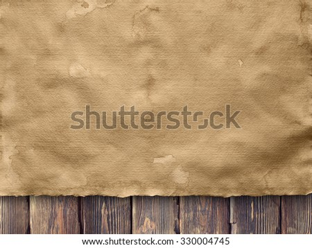 Creased sheet of handmade paper on wooden wall background - stock photo