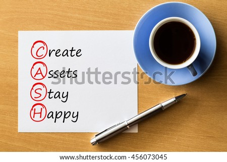 Create Assets Stay Happy (CASH) - handwriting on paper with cup of coffee and pen, acronym business concept