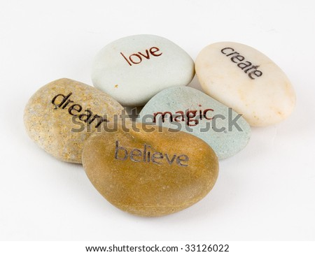 Create, magic, believe, dream, and love wording engraved on stones. - stock photo