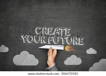 Create your future concept on black blackboard with businessman hand holding paper plane - stock photo