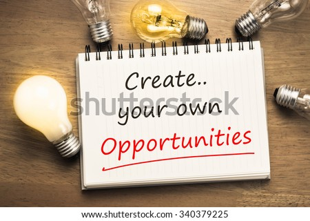 Create Your Own Opportunities as motivated memo on notebook with light bulbs - stock photo