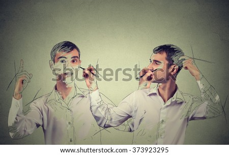 Create yourself concept. Good looking young man drawing a picture, sketch of himself on grey wall background. Human face expressions, creativity - stock photo