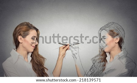 Create yourself, your future destiny, image, career concept. Attractive young woman drawing a picture, sketch of herself on grey wall background. Human face expressions, determination, creativity - stock photo