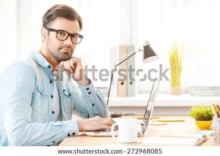 Creating new vision. Handsome young man in shirt and eyewear working on laptop and looking at camera while sitting at his working place - stock photo