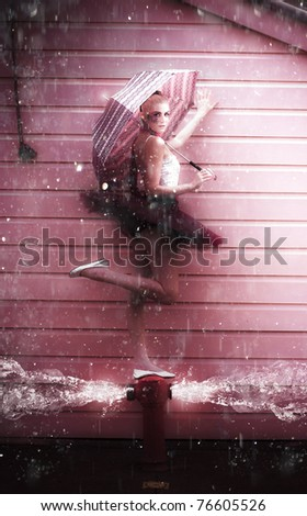Creative Abstract Art Of A Fashion Dance With A Water Dancer Ballerina Woman With Umbrella Dancing In The Pouring Rain On A Burst Fire Hydrant Flooding Water - stock photo