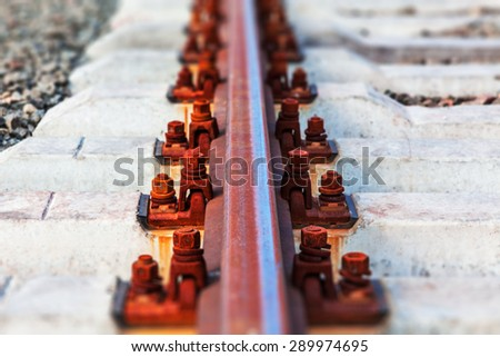 Creative abstract railway transportation industry and railroad cargo shipping business infrastructure industrial concept: macro view of metal train rail and sleepers with selective focus effect - stock photo
