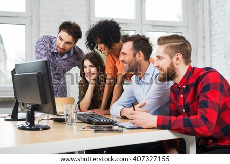 Creative agency concept - casual business people working together with computer in office - stock photo