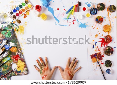 Creative art concept with colorful paints over white paper - stock photo