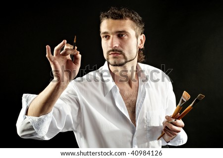 creative artist in a white shirt on a black background with a brush - stock photo