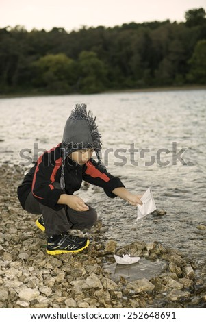 Creative boy playing paper boats at a lake. - stock photo
