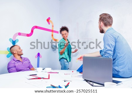 Creative brainstorming. Group of cheerful business people in smart casual wear discussing infographics and writing on the board in the meeting room - stock photo