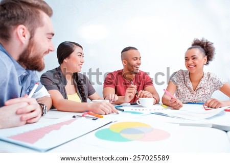 Creative brainstorming. Top view of the group of cheerful business people in smart casual wear discussing analytical infographics while having a brain storming in the meeting room - stock photo