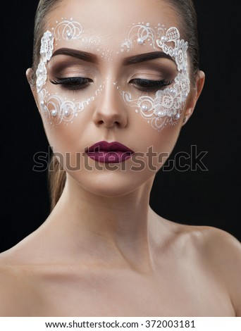 Creative bridal. Vertical shot of a model wearing professional artistic makeup with lace elements - stock photo