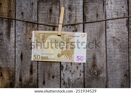 Creative business finance making money concept. Money on a clothespin on a wooden background. Euros - stock photo