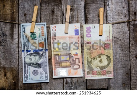 Creative business finance making money concept. Money on a clothespin on a wooden background . US dollars, euros, ukrainian hrivna - stock photo