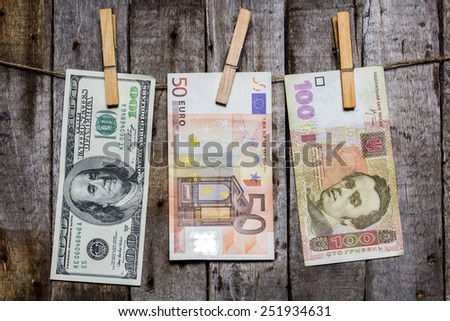 Creative business finance making money concept. Money on a clothespin on a wooden background. US dollars, euros, ukrainian hrivna - stock photo