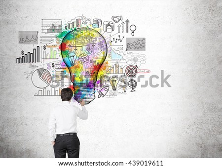 Creative business idea concept with businessman drawing colorful light bulb sketch and business charts on concrete background - stock photo