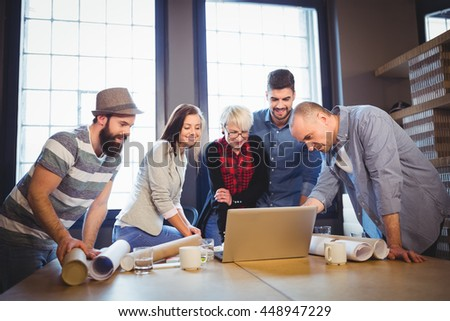 Creative business people discussing over laptop at desk in office - stock photo
