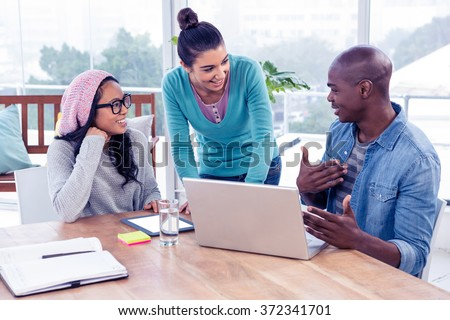 Creative business people sitting in meeting at bright office - stock photo
