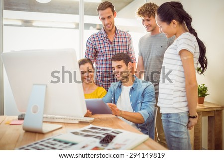 Creative business team gathered around a tablet in the office - stock photo