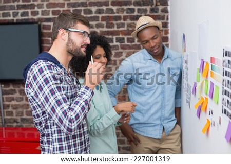 Creative business team looking at sticky notes on wall - stock photo