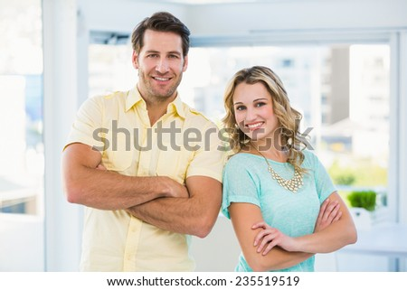 Creative business team posing with arms crossed in office - stock photo