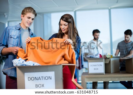Creative business team sorting clothes in donation box in office