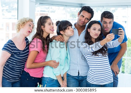 Creative business team taking a selfie in the office - stock photo