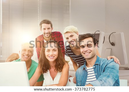 Creative business team using laptop in meeting against computers and headsets - stock photo
