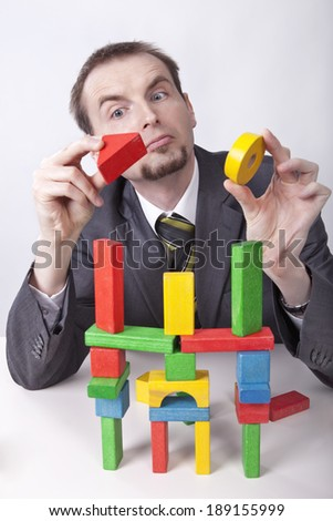 Creative businessman builds the castle from toy's blocks in the office - stock photo