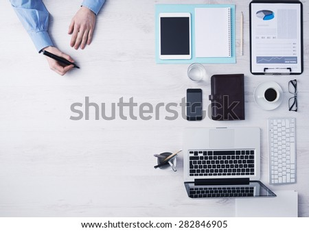 Creative businessman working at office desk and sketching with a black marker, computers and other objects on the right, hands detail top view - stock photo