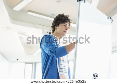 Creative businessman writing on presentation board in office - stock photo