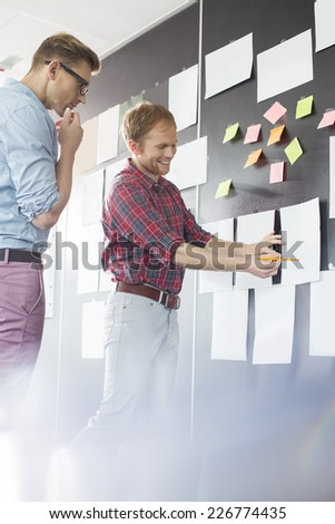Creative businessmen discussing over document on wall in office - stock photo