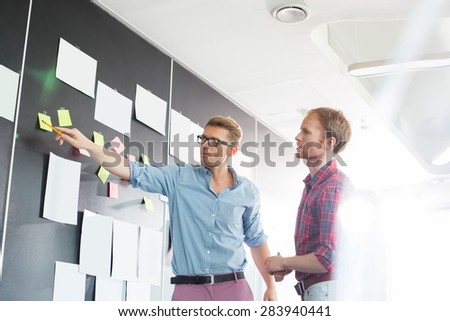 Creative businessmen discussing over sticky paper on wall in office