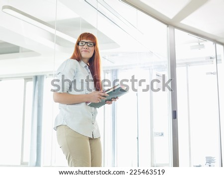 Creative businesswoman looking away while holding files in office - stock photo