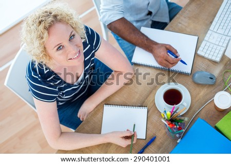 Creative businesswoman smiling at the camera in a meeting - stock photo