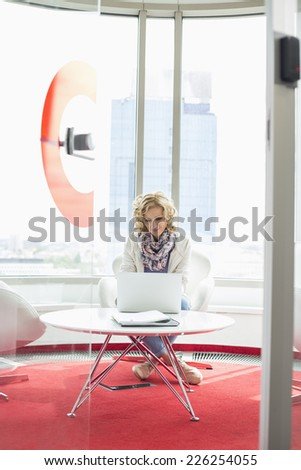Creative businesswoman using laptop in office - stock photo