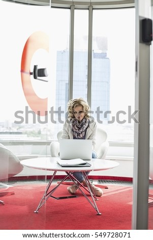 Creative businesswoman using laptop in office