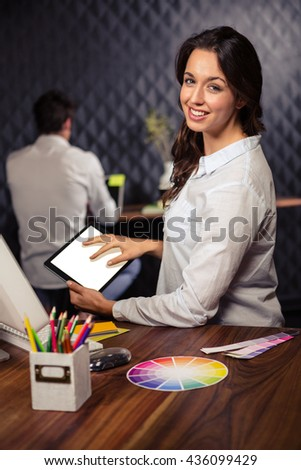 Creative businesswoman working on graphic tablet in office - stock photo