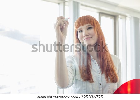 Creative businesswoman writing on glass wall in office - stock photo