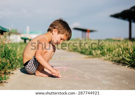Creative child. Little boy painting with colorful chalks outdoors in summer - stock photo