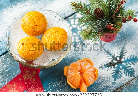 Creative Christmas and New Year decoration with orange cakes, red ribbon, peeled tangerine, spruce tree branches, red berries in a decorative bucket placed on aged blue wooden surface with snowflakes - stock photo