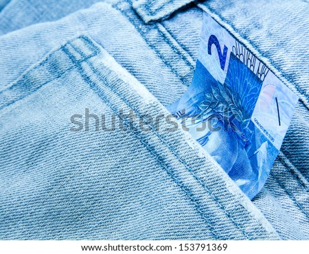 Creative composition of 2 Reais on the jeans - stock photo